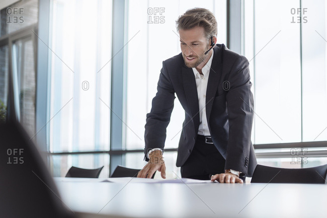 Businessman with bluetooth headset standing in conference room explaining