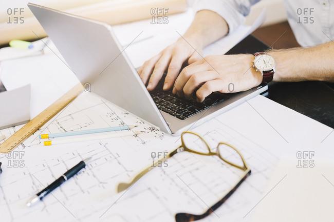 Man using laptop next to construction plan at desk