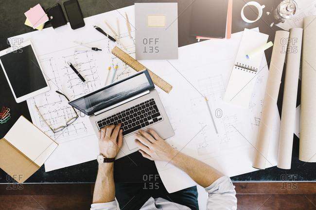 Man using laptop next to construction plan at desk- top view