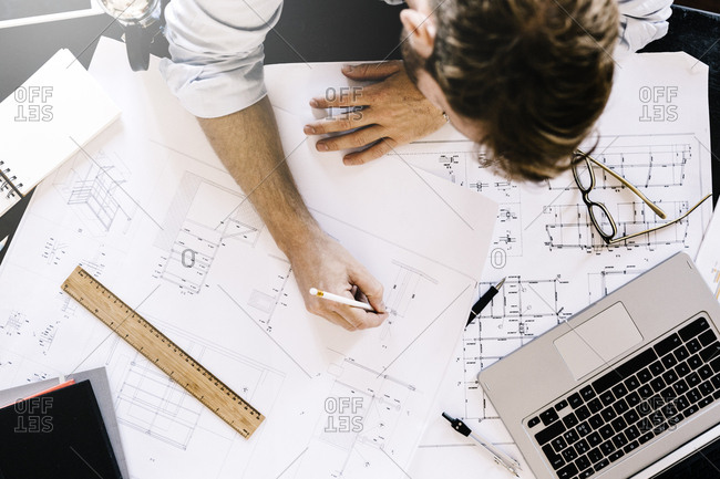 Man working on construction plan at desk- top view