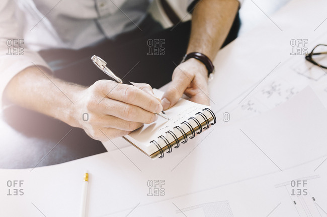 Architect taking notes at desk