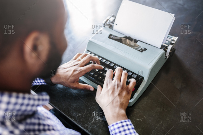 Close-up of man at desk using typewriter