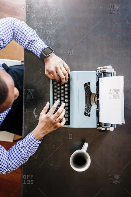 Young man at desk using typewriter