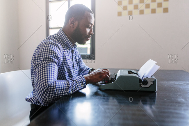 Young man at desk using typewriter