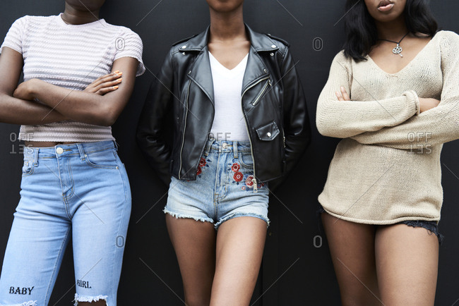 Three friends standing side by side against black background- partial view