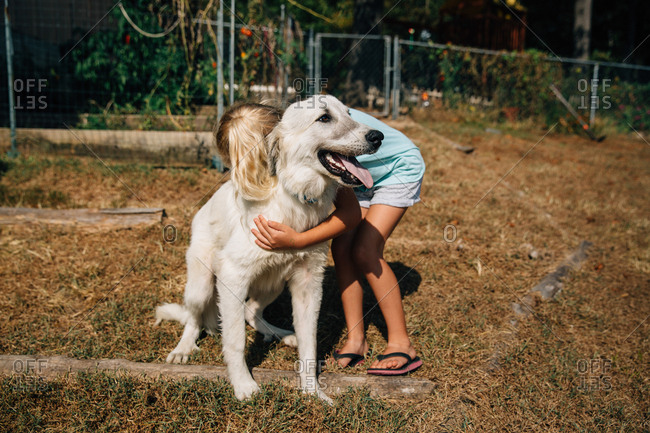 Girl hugs white dog in backyard