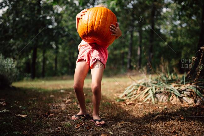 Girl carries large pumpkin