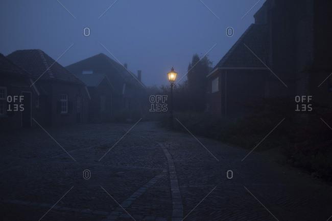Misty street in old village with illuminating lanterns