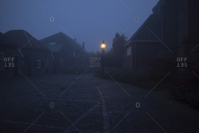 Misty street in old village with illuminating lanterns