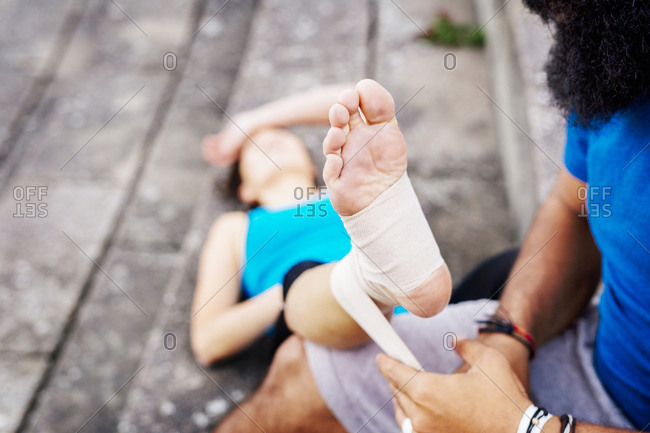 Man wrapping foot of woman in bandage