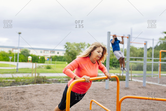 Woman and man exercising in park