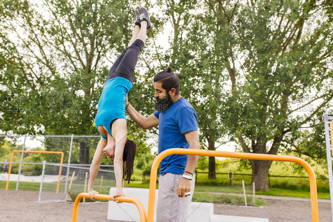 Man helping woman doing handstand