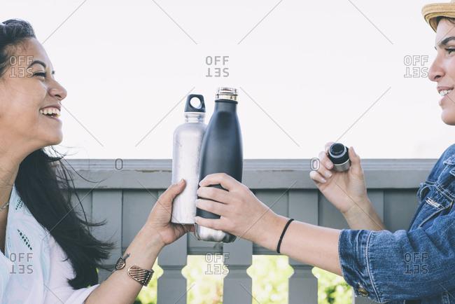 Happy female friends toasting water bottles
