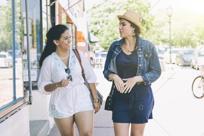 Happy female friends talking while walking on sidewalk in city