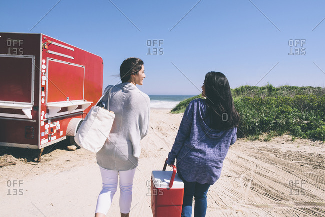 Rear view of female friends walking at beach on sunny day