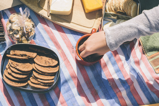 Cropped image of female hand picking snacks from cup during picnic at beach