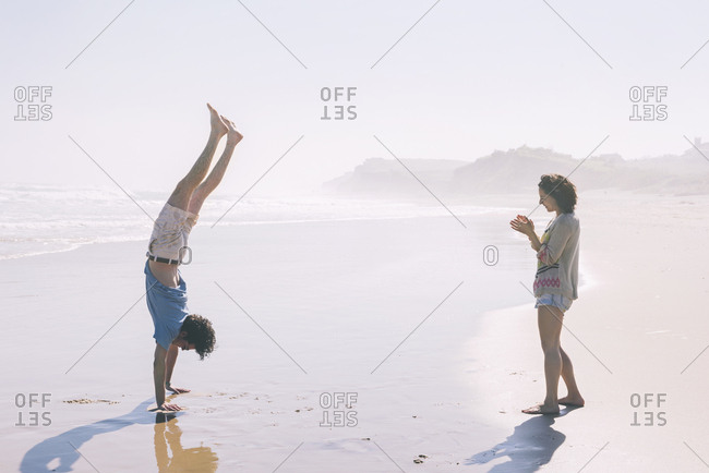 Side view of woman applauding for man doing handstand on shore at beach
