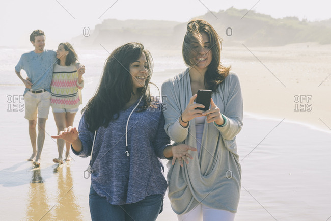 Friends walking on beach on sunny day