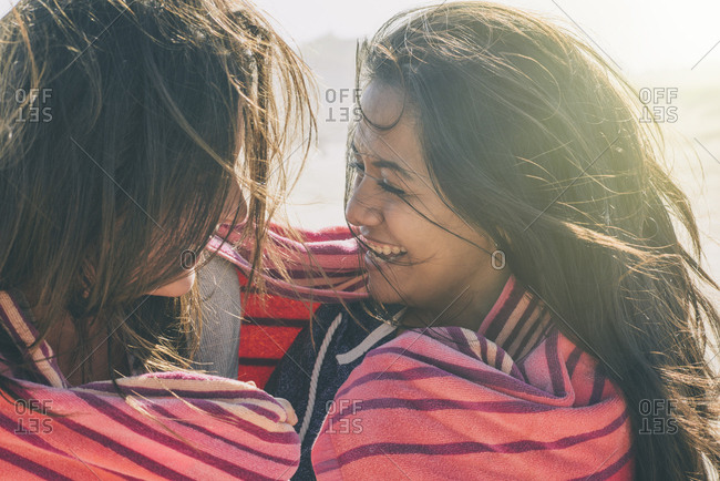Close-up of happy female friends wrapped in blanket at beach