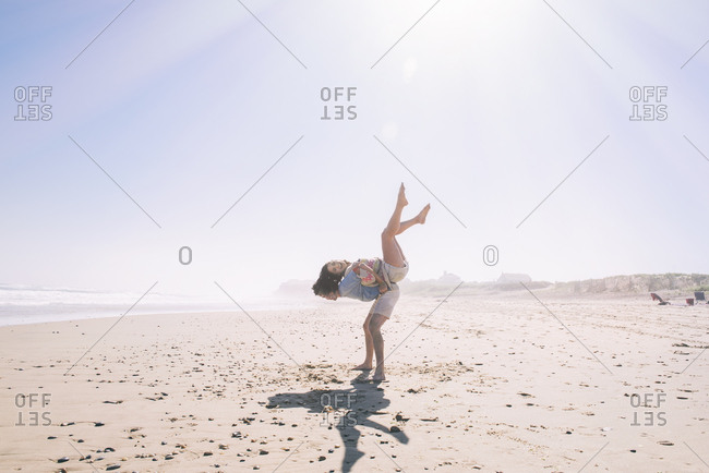 Happy young man lifting woman on back at beach during sunny day