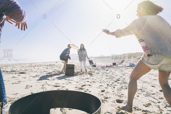 Happy male and female friends playing with flying disc at beach on sunny day