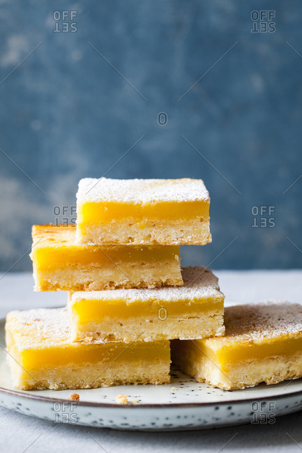 Stacked lemon squares on a blue background