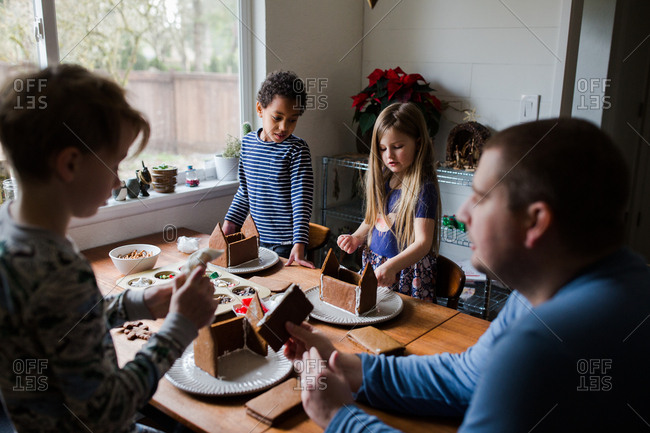 Father and children assembling gingerbread houses