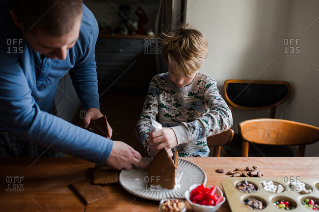 Father and son assembling a gingerbread house