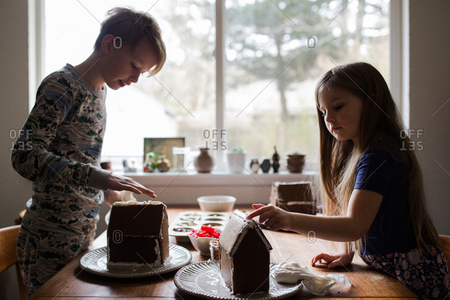 Brother and sister making gingerbread houses