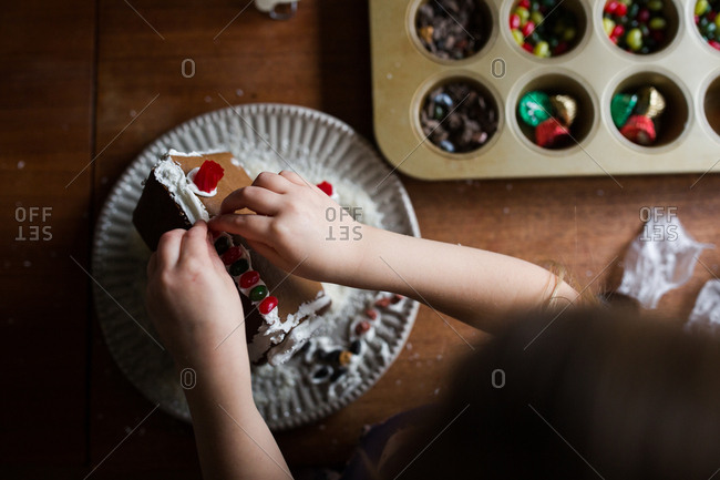 Overhead view of girl making a gingerbread house