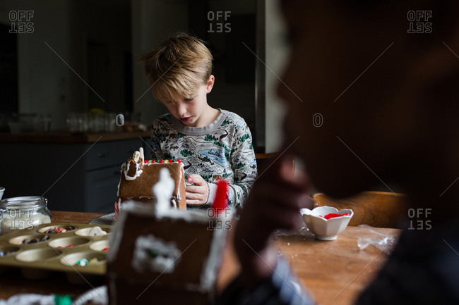 Boy assembling a gingerbread house