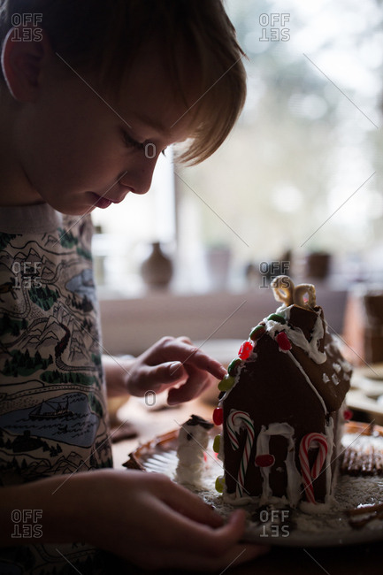 Boy building a gingerbread house