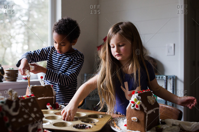 Two girls building gingerbread houses