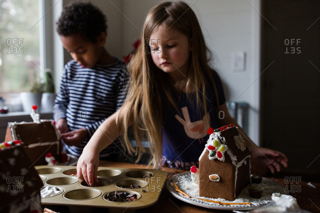 Two girls making gingerbread houses