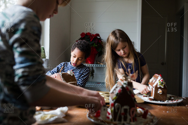 Three children building gingerbread houses