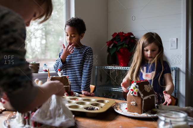 Three children making gingerbread houses
