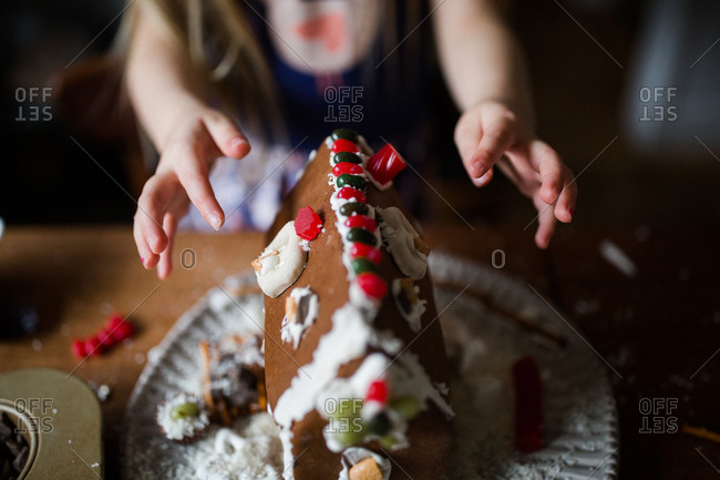 Little girl decorating a gingerbread house