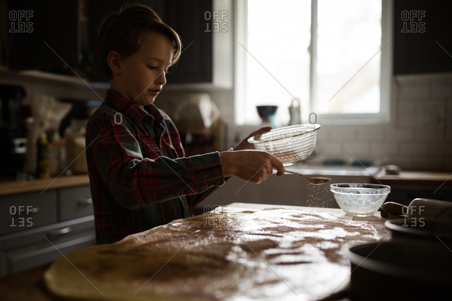 Boy sprinkling sugar mixture on dough for cinnamon rolls
