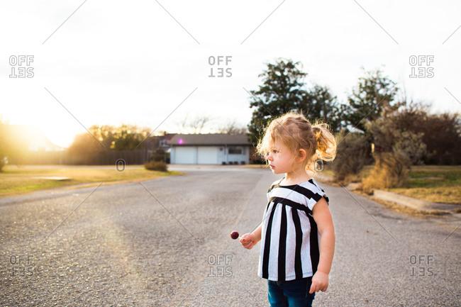 Toddler girl holding a lollipop