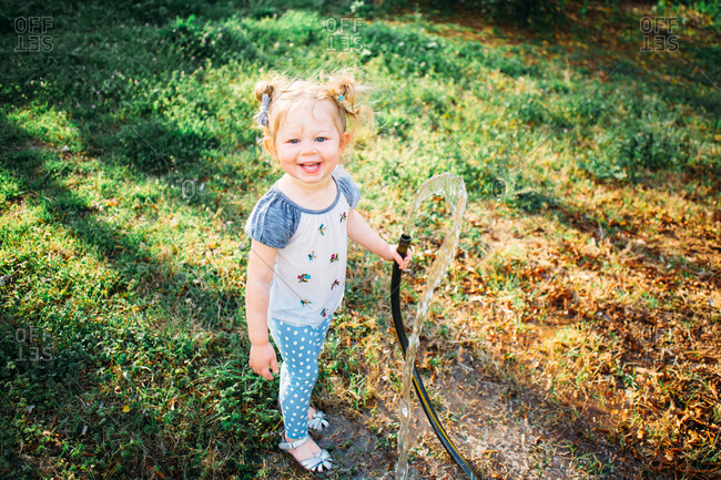 Smiling toddler girl playing with a garden hose