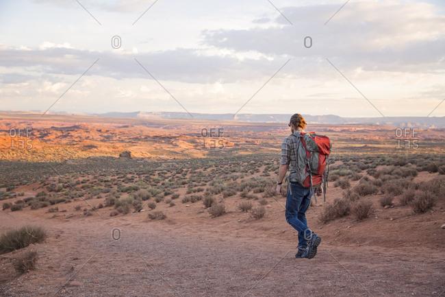 Man hikes a red dirt trail