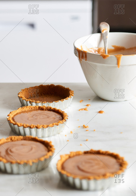 Tart cases filled with salted caramel mixture and a bowl of salted caramel sauce