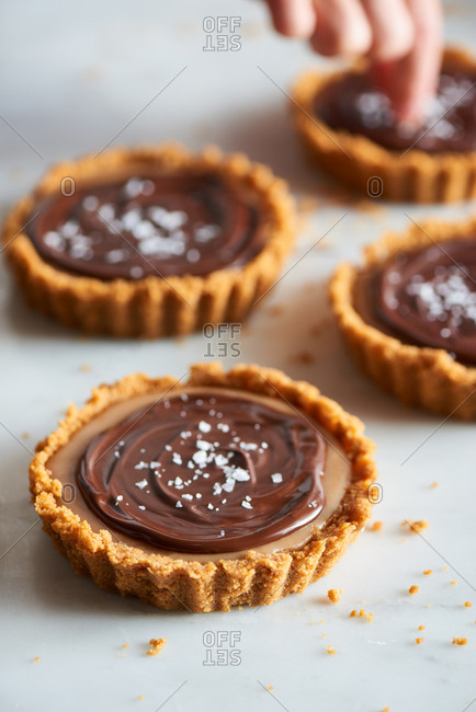 Salt flakes being added to chocolate and salted caramel tarts