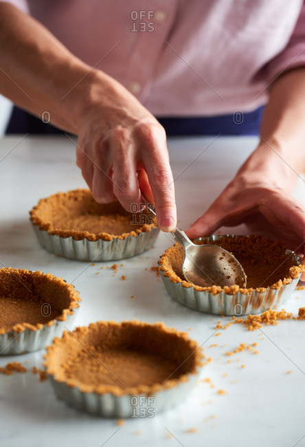 Woman pressing a biscuit base mixture into small tart cases