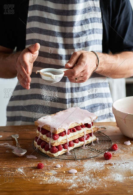 Man sieving icing sugar over a raspberry and cream mille feuille patisserie