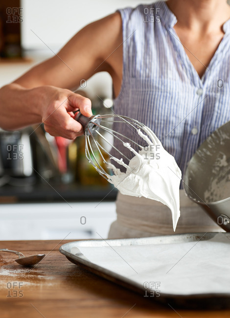 Woman holding a mixer whisk covered in vanilla meringue mixture