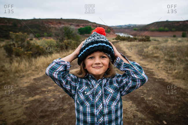Portrait of a little boy outdoors wearing thick knit hat