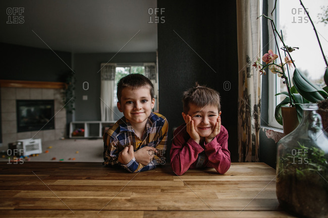 Two boys sitting at table smiling