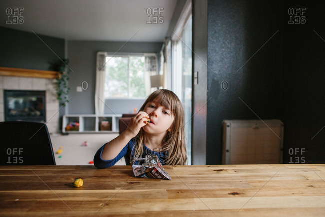 Little girl sitting at table eating a snack