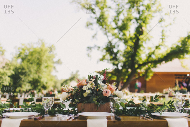 Floral centerpiece on outdoor table at a wedding reception